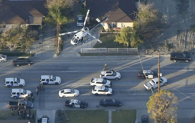 A police helicopter flies over emergency vehicles during a manhunt which followed a mass shooting in San Bernardino