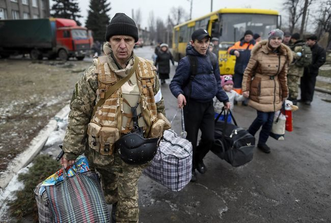 A member of the Ukrainian armed forces assists local residents onto a bus to flee the military conflict, in Debaltseve