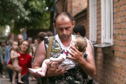 A Russian police officer carries a released baby from a school seized by heavily armed masked men and women in the town of Beslan in the province of North Ossetia near Chechnya, in this September 2, 2004 file photo.    Viktor Korotayev: The Beslan school siege took place on September 1, 2004 during a festive ceremony to launch the new academic year at school No.1. Pro-Chechen gunmen seized the school and took 1,300 hostages on the first day. Some 331 people were killed, half of them children.   On the second day of the siege, the captors were convinced to free several women with babies, so when a fighter of a special task unit was seen leaving the building with a child in his hands, there was hope that children could be saved.  I think that was why this photo was published on the front pages of numerous publications all over the world.  Throughout my career I've covered many difficult stories such as military conflicts in different countries, disasters, hostage situations. The Belsan tragedy remains the biggest psychological trauma I have experienced.    REUTERS/Viktor Korotayev/Files   (RUSSIA - Tags: CIVIL UNREST CRIME LAW TPX IMAGES OF THE DAY)  ATTENTION EDITORS - THIS PICTURE IS PART OF PACKAGE '30 YEARS OF REUTERS PICTURES'  TO FIND ALL 56 IMAGES SEARCH '30 YEARS'