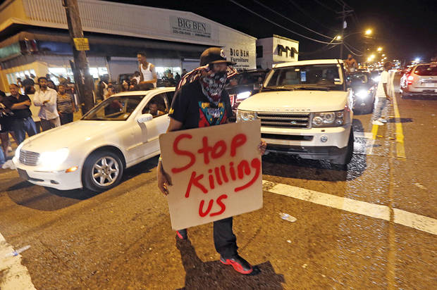 Protestors congregate at N. Foster Dr. and Fairfields Ave., the location of the Triple S convenience store in Baton Rouge, La., Wednesday, July 6, 2016. Alton Sterling, 37, was shot and killed outside the store by Baton Rouge police, where he was selling CDs. (AP Photo/Gerald Herbert)