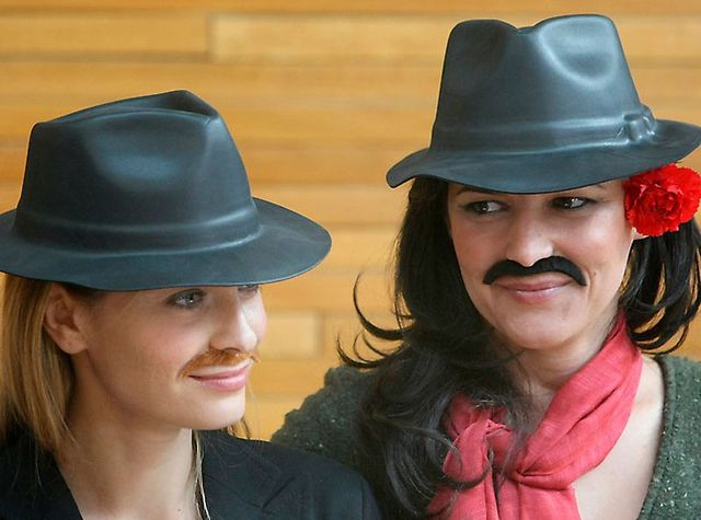European Parliament members Franziska Brantner, of Germany, left and Marisa Matias of Portugal, right, dressed as men wearing a hats and a moustaches, prepare to attend the European Parliament session, Tuesday March 8, 2011, in Strasbourg, eastern France. Several women members of parliament, dressed as men, were asking for equal pay for men and women on International Woman's Day. (AP Photo/Christian Lutz)