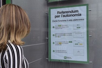 A woman looks at a poster explaining how to vote for a referendum in Italy's northern region of Lombardy to request more autonomy from central government, on October 13, 2017 in Milan.  A referendum will be held on October 22, 2017 in the Italian regions of Lombardy and Veneto, both ruled by rightwing party Northern League, to ask for more fiscal autonomy and more powers to decide how to allocate financial resources. / AFP PHOTO / MIGUEL MEDINA
