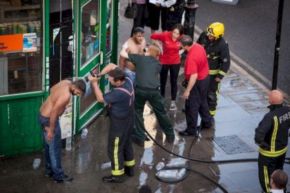 CAPTION CORRECTION BYLINE SHOULD BE Liam Creighton/LNP © Licensed to London News Pictures. 25/07/2017. London, UK. Two victims of what is thought to have been an acid attack have water poured on their heads by a firemen - on the side of the road in Bethnal Green. Two men have been taken to hospital after flagging down police for help. Photo credit: Liam Creighton/LNP