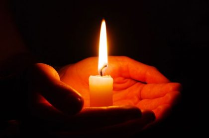 Burning of the candle in a hand in darkness