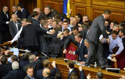 "Deputies of the opposition fight with deputies of the majority for a second time in two days, during the second session of the newly elected Ukrainian parliament in Kiev on December 13, 2012.  The opening session of the Verkhkovna Rada began in a typically raucous fashion, after the October 28 parliamentary elections which were condemned by the West as a setback for democracy.  In the meantime, a fight erupted in the chamber between opposition MPs and two deputies whom they accused of defecting to the pro-government camp. Several lawmakers from the opposition nationalist Svoboda group chased two men they called ""turncoats"" -- a father and a son -- to prevent them from taking the oath.   AFP PHOTO//SERGEI SUPINSKY        (Photo credit should read SERGEI SUPINSKY/AFP/Getty Images)"