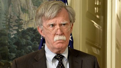 "WASHINGTON, DC - APRIL 13: National Security Advisor John Bolton listens to remarks by U.S. President Donald Trump as he speaks to the nation, announcing military action against Syria for the recent apparent gas attack on its civilians, at the White House, on April 13, 2018, in Washington, DC. President Trump announced that a joint operation of ""precision strikes"" is underway in Syria with armed forces from the United Kingdom and France.  (Photo by Mike Theiler - Pool/Getty Images)"